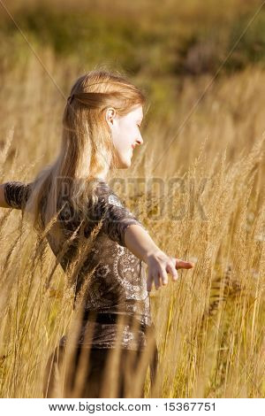 Happy young woman in a filed.