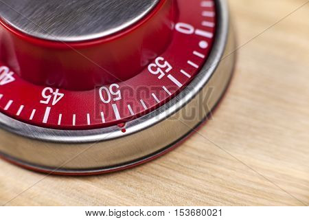 Macro view of a red kitchen egg timer showing 50 minutes on wooden background