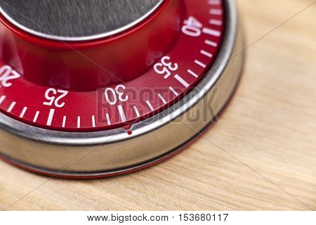 Macro view of a red kitchen egg timer showing 30 minutes on wooden background