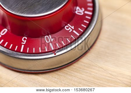Macro view of a red kitchen egg timer showing 10 minutes on wooden background