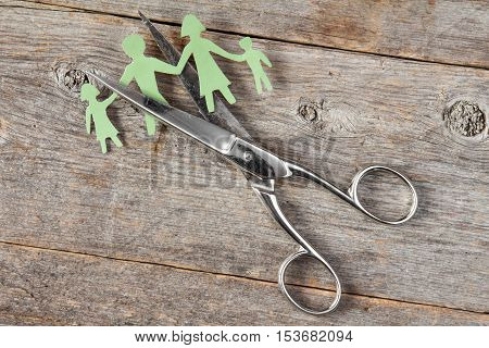 Scissors cutting paper cut of family. Broken family or divorce concept.