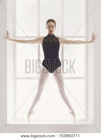 Classical Ballet dancer portrait. Beautiful graceful ballerine in black practice releve ballet position near large window in light hall. Ballet class training, high-key soft toning. Vertical image