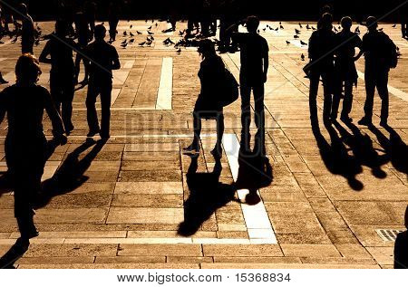 Walking people silhouette. Red sunset light.
