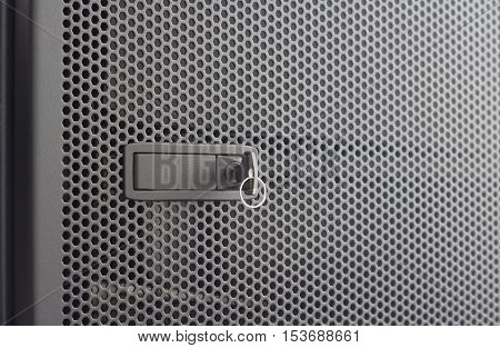 Door perforated of server rack cabinet. The key is inserted into the door lock. Side lighting and shallow DOF