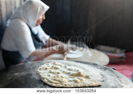 Granny chef cook Turkish pancake Gozleme on the stove. The national dish of Turkish cuisine.