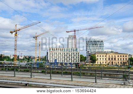 Berlin Germany - August 14 2016: Berlin under construction. View of new modern buildings and cranes from Hauptbahnhof (Central station) with Hotel Ibis in the middle and Social Court to the right.