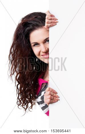 Portrait of a happy young casual woman holding a blank signboard, isolated on white background. Closeup portrait of a beautiful brunette teen hiding behind empty white sign.