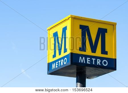 A large yellow and blue Metro railway station sign denoting the entrance to a city train station with a blue sky background.