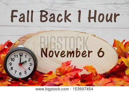 Daylight savings time message Some fall leaves an alarm clock and wood plaque on weathered wood with text Fall Back 1 hour