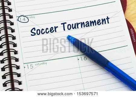 Your soccer tournament schedule a day planner with blue pen with text Soccer Tournament
