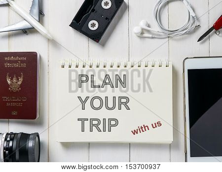 Plan your trip text on a book surrounding with travel equipments. Travel agency advertising banner for traveller trip planing.