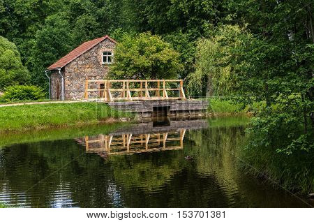 Pushkinskiye GoryRussia-June 142016: The bridge over the canal and the old house on the territory of Mikhailovskoye Pushkin's places Pskov region Russia. poster