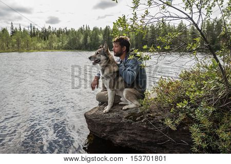 Handsome man and dog are sitting on the stone near of lake and looking into the distance