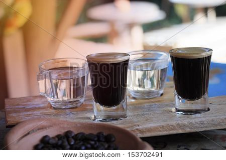 Shot of espresso coffee and roasted coffee beans on wooden table and sunlight background