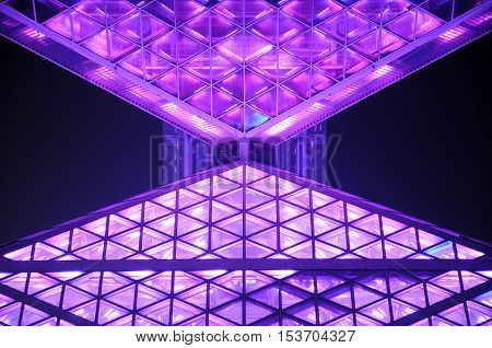 Abstract architecture light up at night with pinkish and purple lighting.
