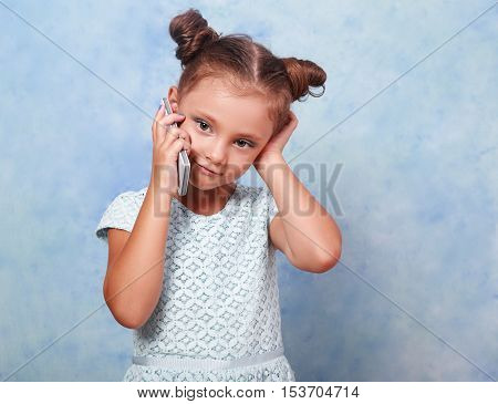 Thinking Kid Girl Talking On Mobile Phone With Happy Smile On Blue Background With Empty Copy Space