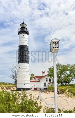 A birdhouse on a tall pole stand before the Big Sable Point Lighthouse in Michigan's Ludington State Park on the Lake Michigan coast.