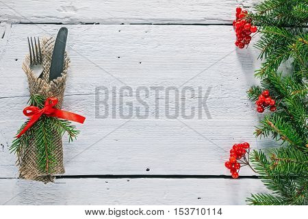 Christmas frame of evergreen twigs with silverware on white painted wood. Overhead view