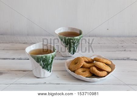 tea biscuits on white background white and green ceramic cups ceramic ware on a white background
