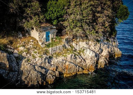 Small old stone lodge on a rocky shore close to a lake river or sea. Small shed with closed blue door. Next to the dense forest.