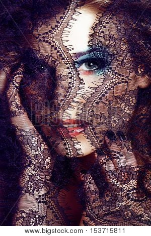 portrait of beauty young woman through lace close up mystery makeup fashion