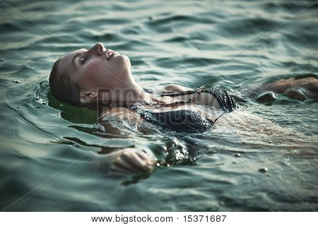 Young woman swimming. Soft green tint.