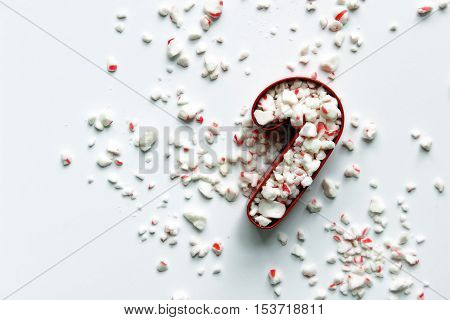 Over head flat lay view of a red candy cane cookie cutter filled with crushed peppermint candy spilling out against background.
