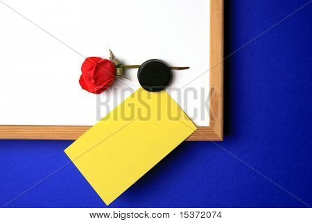 white-board with empty yellow post-it note a magnet and a red rose