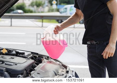 Man filling antifreeze fluid in his car