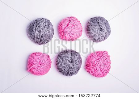 Six yarns on white background, high angle view. Three pink and tree gray wool yarns on white background shot from above. No retouch, studio lighting.
