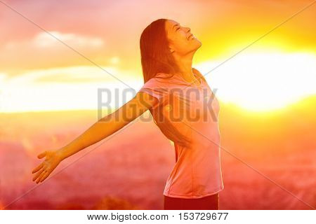 Happy people - carefree woman enjoying free nature at sunset. Freedom, serenity, wellness and spirituality concept - Asian girl with open arms in ecstatic enjoyment praising life to the sky.