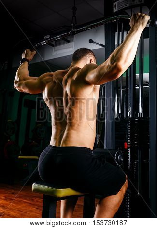 very power athletic guy bodybuilder, execute exercise with gym apparatus, on broadest muscle of back