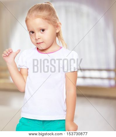 Cute little blond girl in white tank top without a pattern.Girl shows thumb to the side.The concept of pre-school education of the child among their peers . in gaming room with a large arched window.