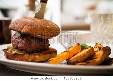 Beefburger with fried sweet potatoes served on a white plate