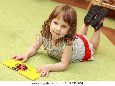 Cute little blonde girl, in a gray summer dress lying on the Mat . The girl examines the application , which she did in Montessori kindergarten.