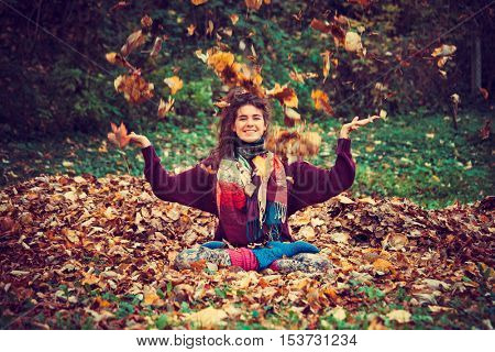 smiling young woman sit in yoga position in autumn leaves in park