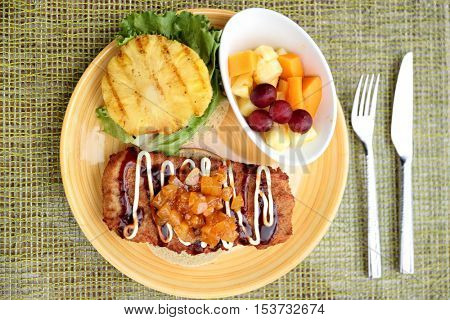 Hawaiian japanese fusion food, Hawaii culture. Restaurant plate closeup of karaage chicken burger, japanese fried chicken specialty with chutney, mayonnais, grilled pineapple and fresh fruits side.