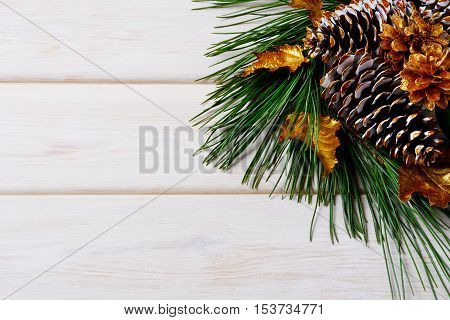 Christmas holiday background with golden decorated fir and pine cones. Christmas decoration with golden decor. Christmas greeting background. Copy space.