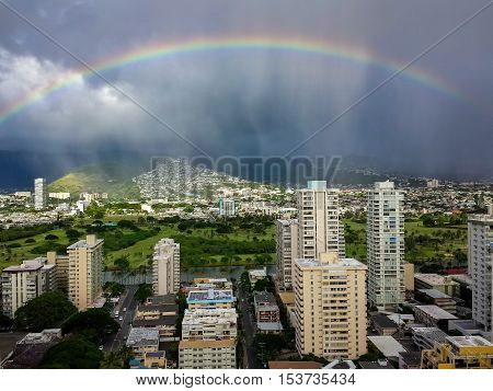 View of the Palolo region that backs against the distant hills. Image features a rainbow, dramatic sky and approaching rain clouds. Taken on the 30th floor of the Hyatt Regency Hotel.