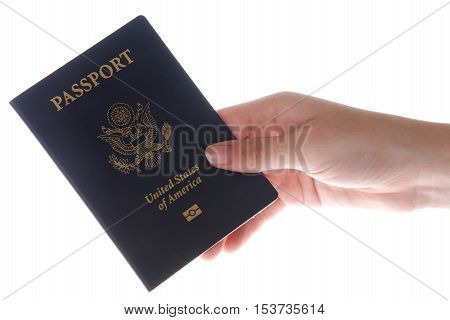 Young female hand presenting a United States passport isolated on a white background. A passport is necessary for travel outside the country including via cruise ships.