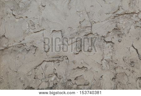 Crumbling grey plaster wall forms an irregular pattern that can be used for backgrounds.