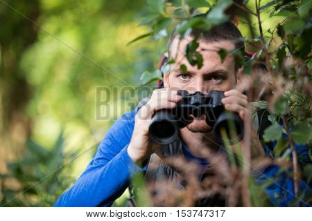 Male hiker looking through binoculars in forest