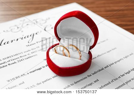 Opened red box with golden wedding rings on marriage contract, closeup