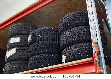 auto service, repair, maintenance and people concept - tires at car shop or warehouse
