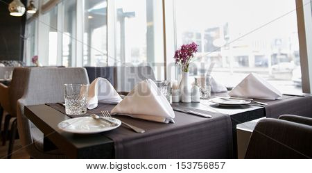 public place, table setting and interior concept - restaurant interior with tables and chairs