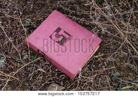 The old soviet book lying on the ground, pink book, grunge, old book