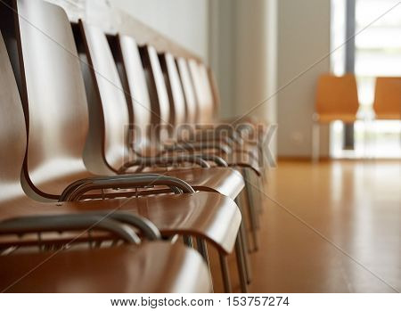 furniture, public places and interior concept - wooden chairs at hospital waiting room