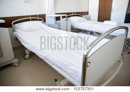 healthcare, medicine and ambulatory concept - hospital ward with clean empty beds