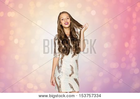 people, style, holidays, hairstyle and fashion concept - happy young woman or teen girl in fancy dress with sequins touching long wavy hair over rose quartz and serenity lights background
