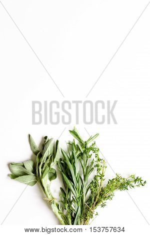 sage, rosemary, thyme - tufts of herbs white background top view